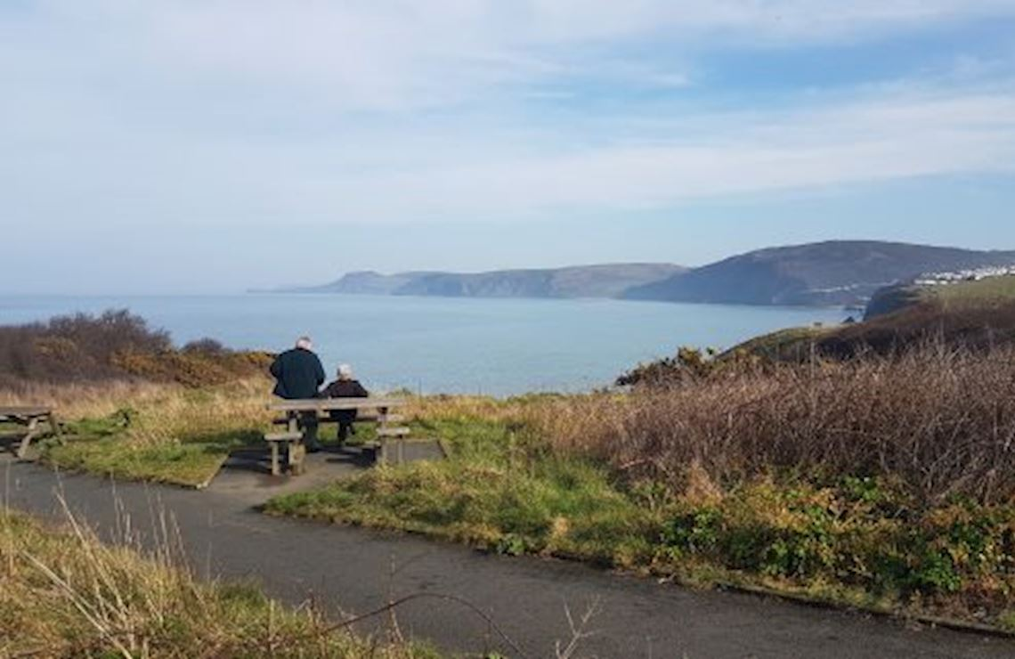 Two people at a picnic bench looking out to sea