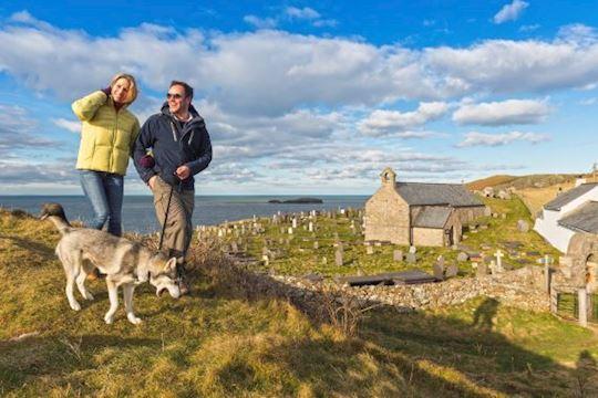 Two people walking dog at Llanbadrig Church Anglesey